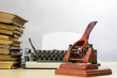 Старый пунш бумаги офиса на деревянном столе Аксессуары офиса дальше Стоковые Изображения RF