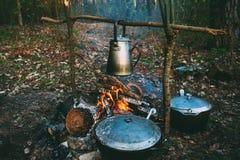 Старый ретро железный чайник лагеря и готовит воду чиреев на огне в лесе Стоковая Фотография RF