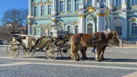 Старый ретро экипаж перед музеем обители Зимнего дворца на квадрате дворца в Санкт-Петербурге, России Историческая старая стоковое фото rf