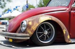 Старый ржавый автомобиль VW Фольксвагена красного цвета осмотренный для места для стоянки восстановления публично Стоковые Фотографии RF