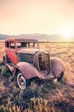 Старый ржавый античный автомобиль покинутый в поле на заходе солнца Стоковые Фото