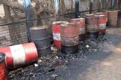 Старый ржавый бочонок вышел в дорогу протекая толстые черные смолка или масло на городскую улицу в Kolkata Стоковые Изображения RF