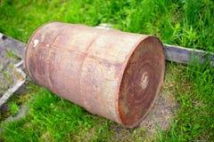 Старый ржавый бочонок против зеленой травы Стоковая Фотография