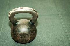 Старый ржавый вес kettlebell на черном поле спортзала с зерном селективного фокуса и фильма Стоковое Изображение