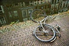 Старый ржавый велосипед лежа около воды Стоковое Изображение RF