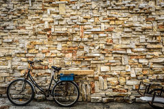 Старый ржавый винтажный велосипед велосипеда и декоративная каменная стена стоковая фотография