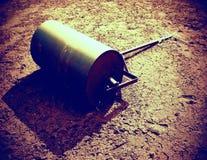 Старый ржавый железный бочонок для обслуживания теннисного корта запущенности Старый сухой красный цвет задавил кирпичи отделывае Стоковое Фото