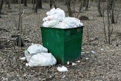 Старый ржавый контейнер отброса зеленого цвета металла полный с пластиковым ненужным положением в загрязнении окружающей среды па стоковые фотографии rf