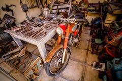 Старый ржавый мотоцикл в сарае с старыми ржавыми инструментами стоковые изображения rf