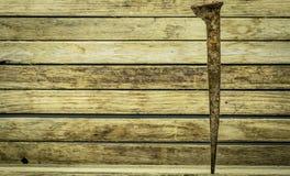 Старый ржавый ноготь на деревянной предпосылке стоковое фото