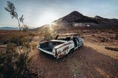 Старый ржавый покинутый автомобиль в пустыне на времени захода солнца стоковые фотографии rf