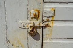 Старый ржавый padlock на деревянных дверях, старая белизна разрушил дверь, Русь Стоковая Фотография