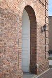 Старый русый вход аркы кирпича к зданию в городе с черной лампой стоковые изображения rf