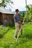 Старый сельский человек используя косу Стоковые Изображения RF