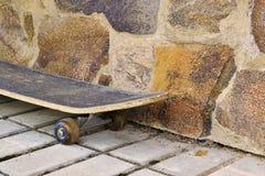 Старый скейтборд от каменной стены Стоковые Изображения RF