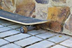 Старый скейтборд от каменной стены Стоковое Изображение RF