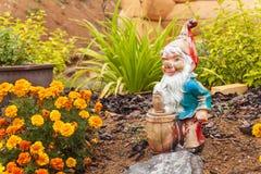 Старый сломанный карлик в саде Украшение в flowerbed Стоковое Изображение RF