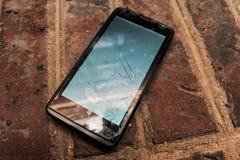 Старый сотовый телефон (smartphone) с сломленным экраном на земле стоковые фотографии rf