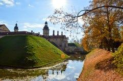 Старый, старый средневековый замок с spiers и башнями, стены камня и кирпич окруженный защитным ровом с водой стоковые фотографии rf