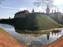 Старый, старый средневековый замок с spiers и башнями, стены камня и кирпич окруженный защитным ровом с водой стоковое фото rf