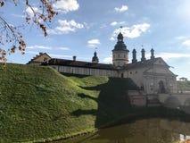 Старый, старый средневековый замок с spiers и башнями, стены камня и кирпич окруженный защитным ровом с водой стоковые изображения