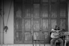 Старый старший азиатский человек сидит газета чтения перед старым vint стоковые изображения