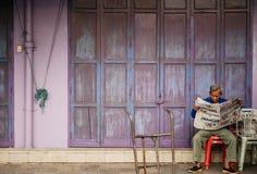 Старый старший азиатский человек сидит газета чтения перед старым vint стоковое фото