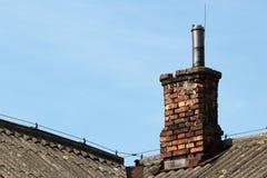 Старый стог дыма кирпича на крыше шифера Стоковое Фото