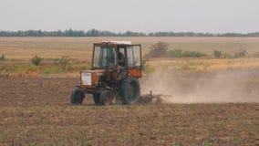 Старый трактор вспахивая поле видеоматериал