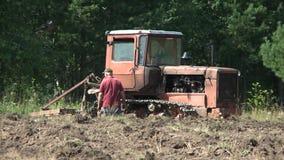 Старый трактор вспахивая почву хуторянин сток-видео