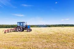 Старый трактор в поле в сене Стоковые Изображения RF