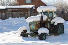 Старый трактор под снегом Стоковые Изображения RF