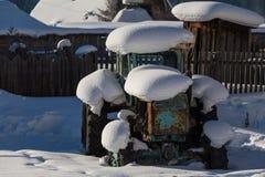 Старый трактор под снегом Стоковые Изображения
