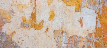Старый треснутый выдержанный затрапезный покрашенный желтый цвет заштукатурил, который слезли предпосылка знамени стены Стоковое Изображение RF