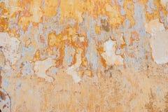 Старый треснутый выдержанный затрапезный покрашенный желтый цвет заштукатурил, который слезли предпосылка стены Стоковая Фотография RF