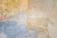 Старый треснутый выдержанный затрапезный покрашенный желтый цвет заштукатурил, который слезли предпосылка стены Стоковое Фото