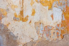 Старый треснутый выдержанный затрапезный покрашенный желтый цвет заштукатурил, который слезли предпосылка стены Стоковое Изображение RF
