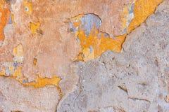 Старый треснутый выдержанный затрапезный покрашенный желтый цвет заштукатурил, который слезли предпосылка стены Стоковые Фотографии RF