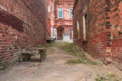 Старый упущенный квартал, разрушенные стены красного кирпича формирует перспективу к парадному входу жилого дома Стоковое Фото
