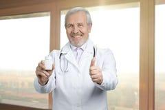 Старый усмехаясь доктор с чонсервной банкой пилюлек и как знак Стоковые Изображения