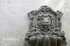 Старый фонтан головы льва, который установлен на бело-серой стене Что не использовано в течение длительного времени стоковое изображение
