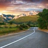Старый хайвей против гор на заходе солнца Стоковые Фотографии RF
