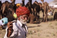 Старый человек Rajasthani на фоне его верблюдов Стоковые Изображения RF