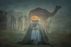 Старый человек Rajasthani на фоне его верблюдов Стоковые Фото
