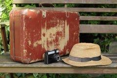 Старый чемодан, шляпа и камера на стенде Стоковая Фотография