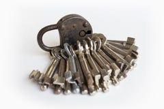 Старый черный padlock и много ключей на белой предпосылке Стоковые Изображения RF