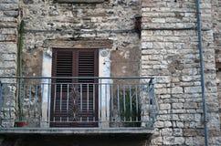 Старый шикарный голубой балкон на каменном доме в маленьком городе Стоковые Фото
