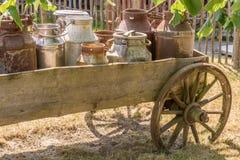 Старый экипаж с маслобойками молока нагруженными как украшение на ферме стоковые фотографии rf