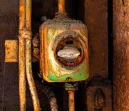 Старый электрический переключатель на ржавой железной стене Стоковые Изображения RF