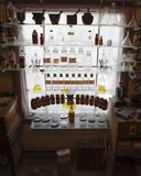Старый apothecary раздражает в освещенном окне Стоковые Фотографии RF